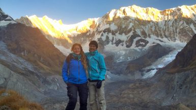 Two female trekkers posing at Annapurna Base Camp, Nepal.