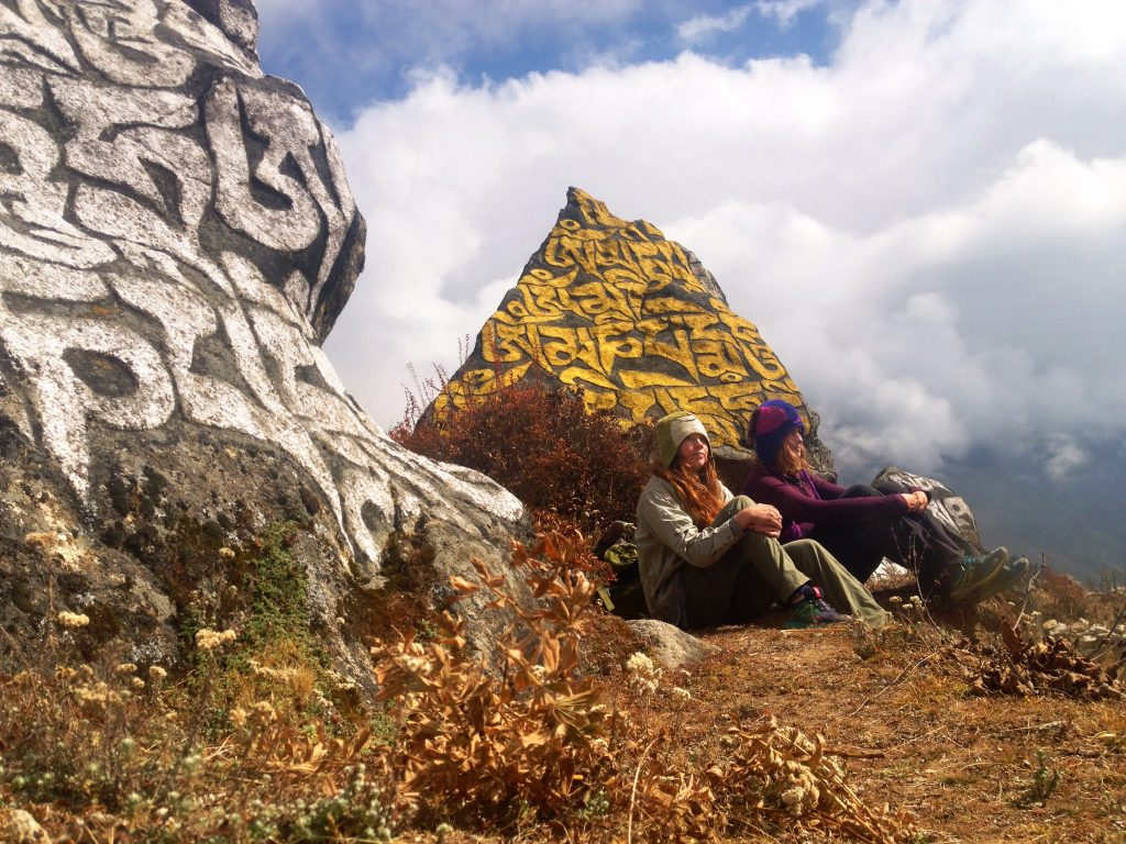 Two girls sit in front of rocks with carved Buddhist scriptures.