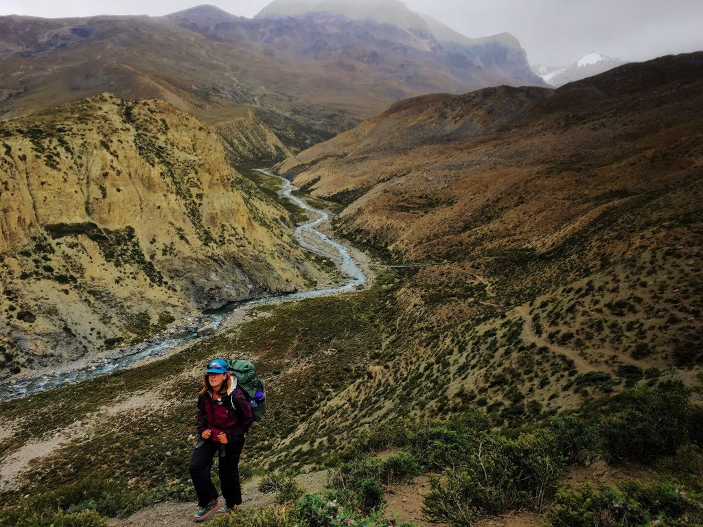 A hiker in Dolpa, Nepal treks above a river and mountains.