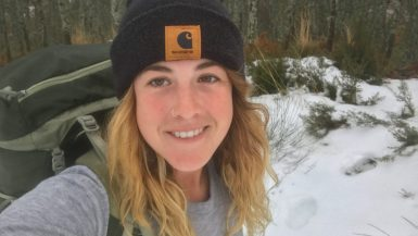 A smiling hiker wearing a backpack, snow is on the ground.