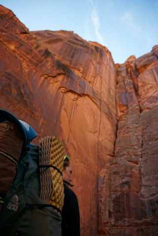 A hiker wears a green backpack and looks up at the slot canyon walls.