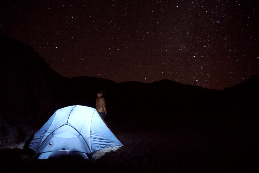 A glowing tent under the stars on the Jebel Sahro Circuit in Morocco's Atlas Mountains.