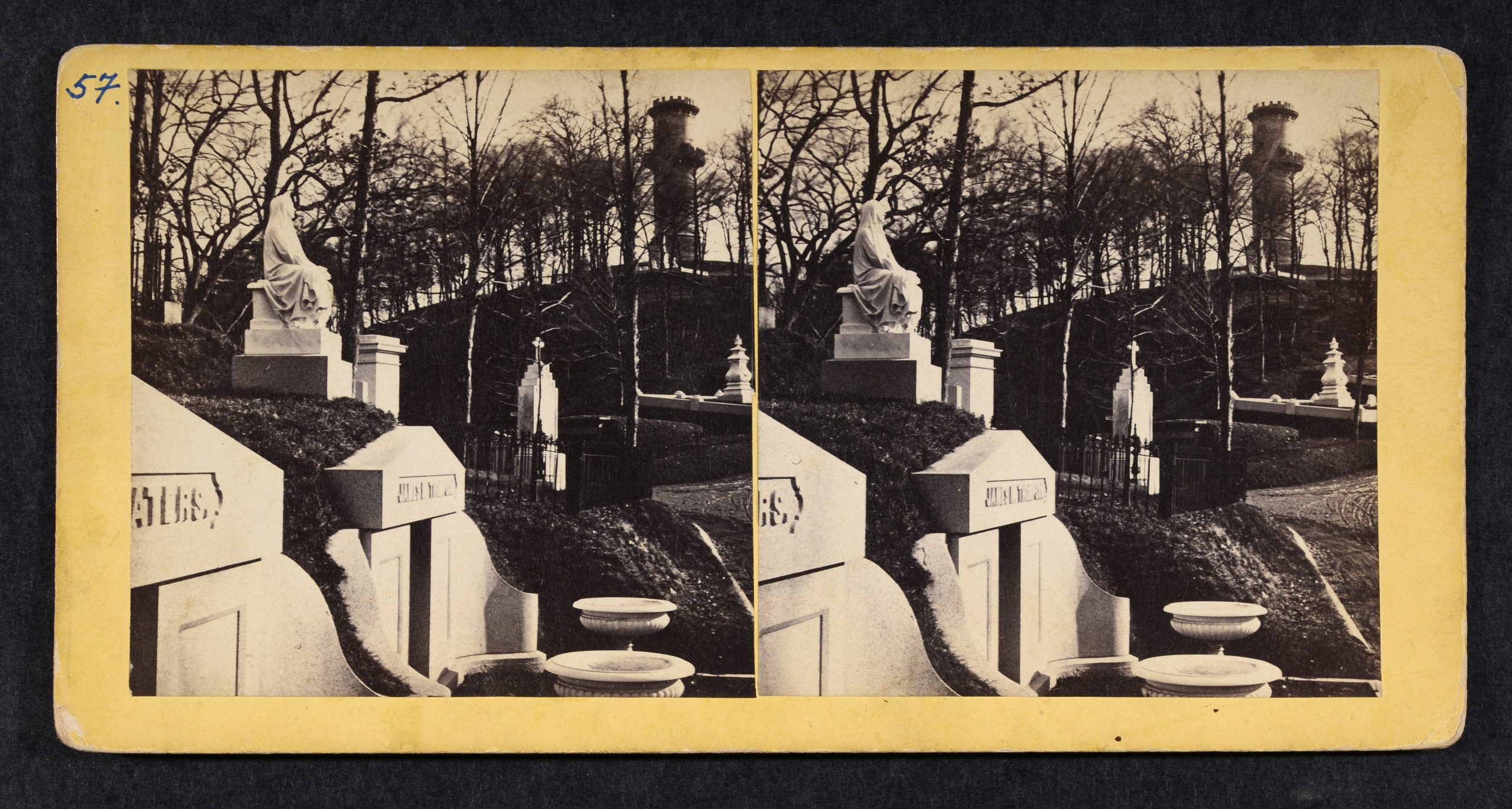 Stereoview of hillside tombs, monuments, trees, large tower in background.