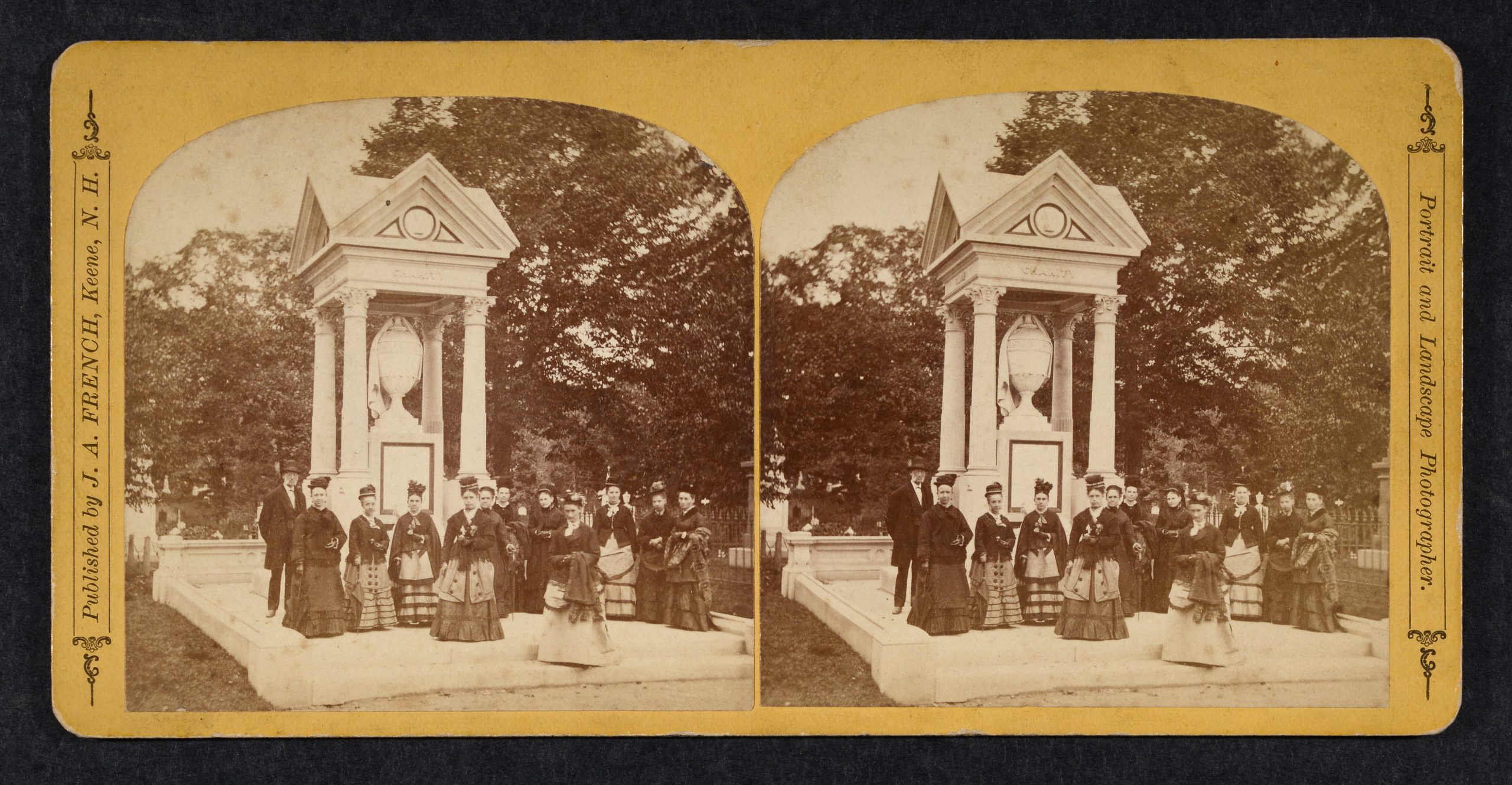 Stereoview of group of 11 women and 1 man in front of large canopy monument.