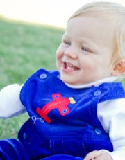 Lucas (1) wears blue overalls with a white turtleneck by Kicky Pants provided by Angels & Rascals.