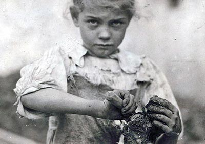 A 7-year-old girl shucks oysters.