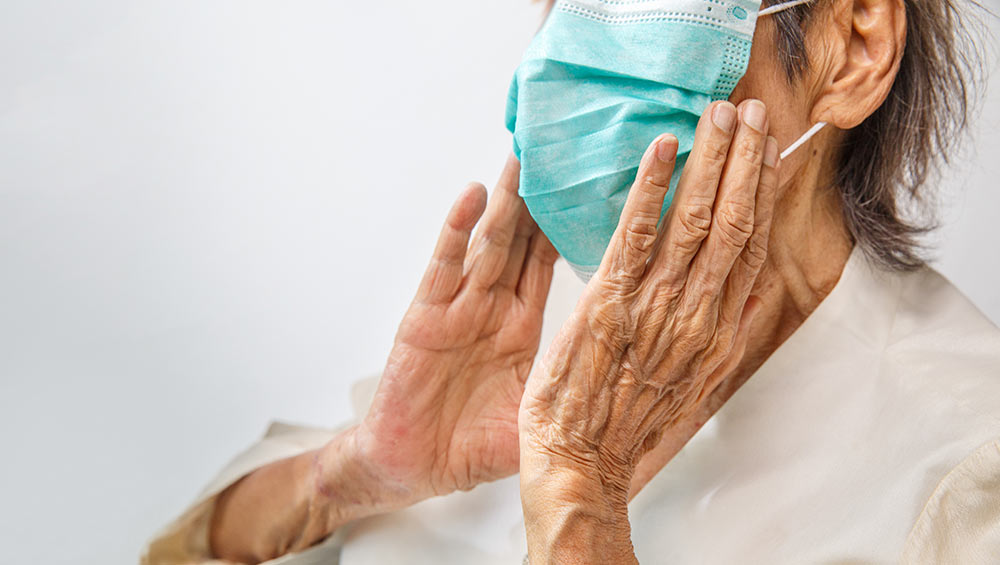 An elderly woman wearing a personal protective mask