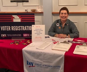 Joan Zaleski, Director of Voter Services at the Charleston Area League of Women Voters manning a voting booth
