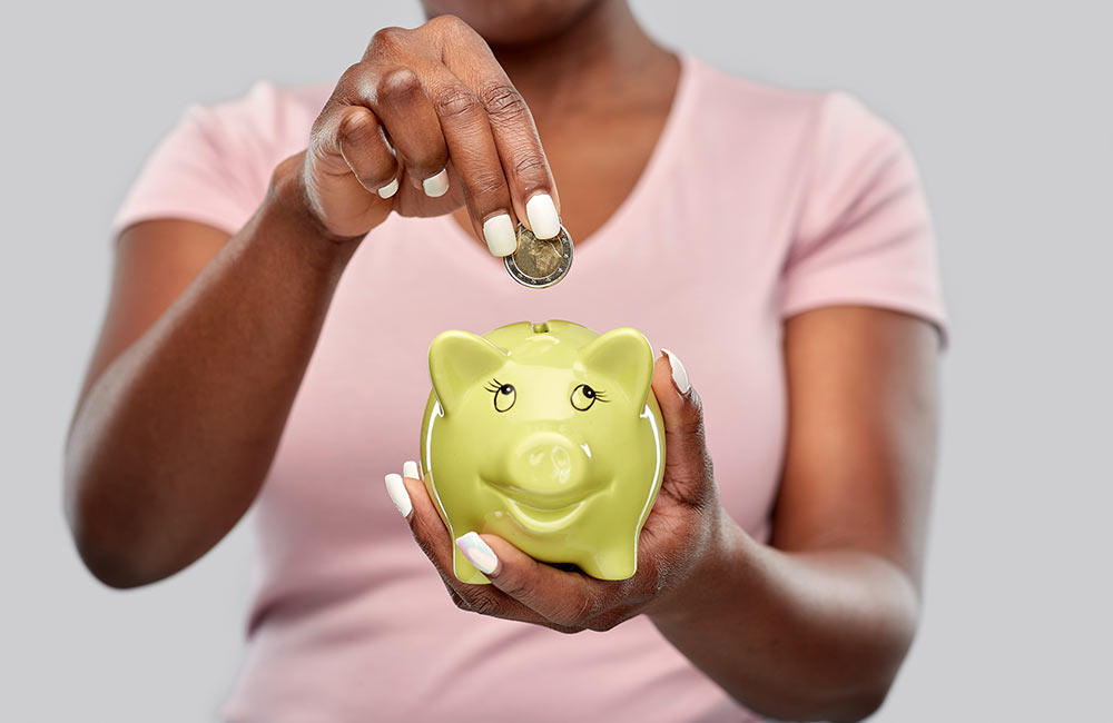 A woman puts a coin into her piggy bank for savings.