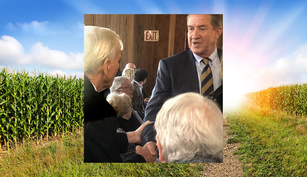 Commissioner Weathers shakes hands with Willie McRae set on background of a corn field.