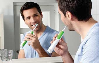 Man using a sonicare powerup toothbrush.