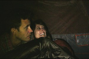 "Bryce Johnson and Alexie Gilmore hide from Bigfoot in a scene from Bobcat Goldthwait's film ""Willow Creek"""