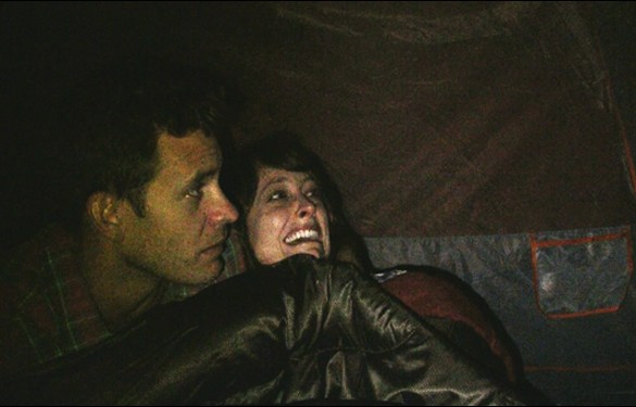 """Bryce Johnson and Alexie Gilmore hide from Bigfoot in a scene from Bobcat Goldthwait's film """"Willow Creek"""""""