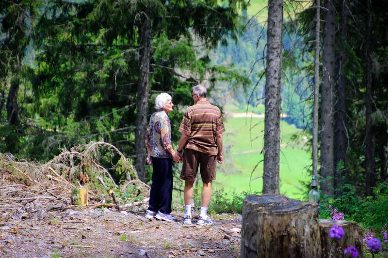Eldery couple hiking in the woods while preventing a fall