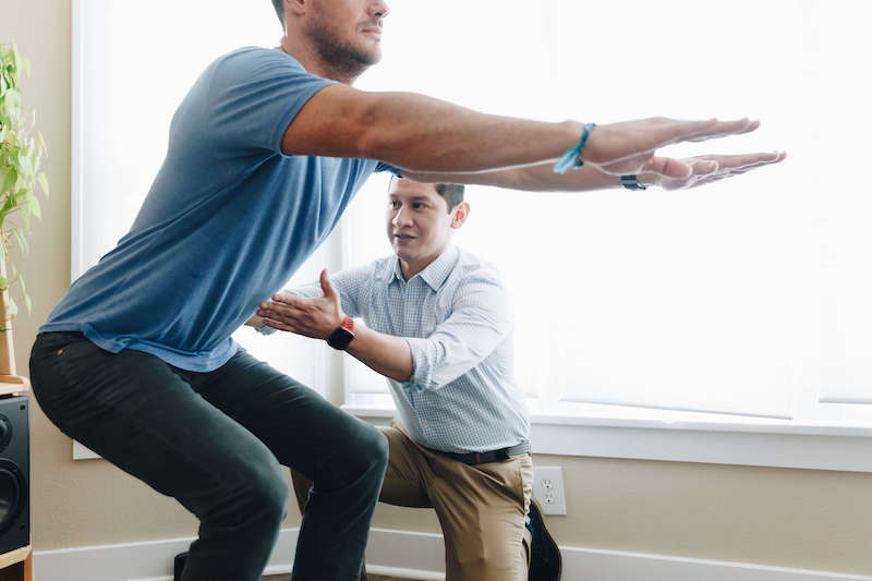 Man learning how to squat with his physical therapist after hip pain