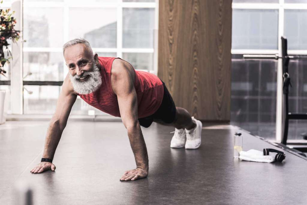 Older man with a beard at the gym doing a pushup