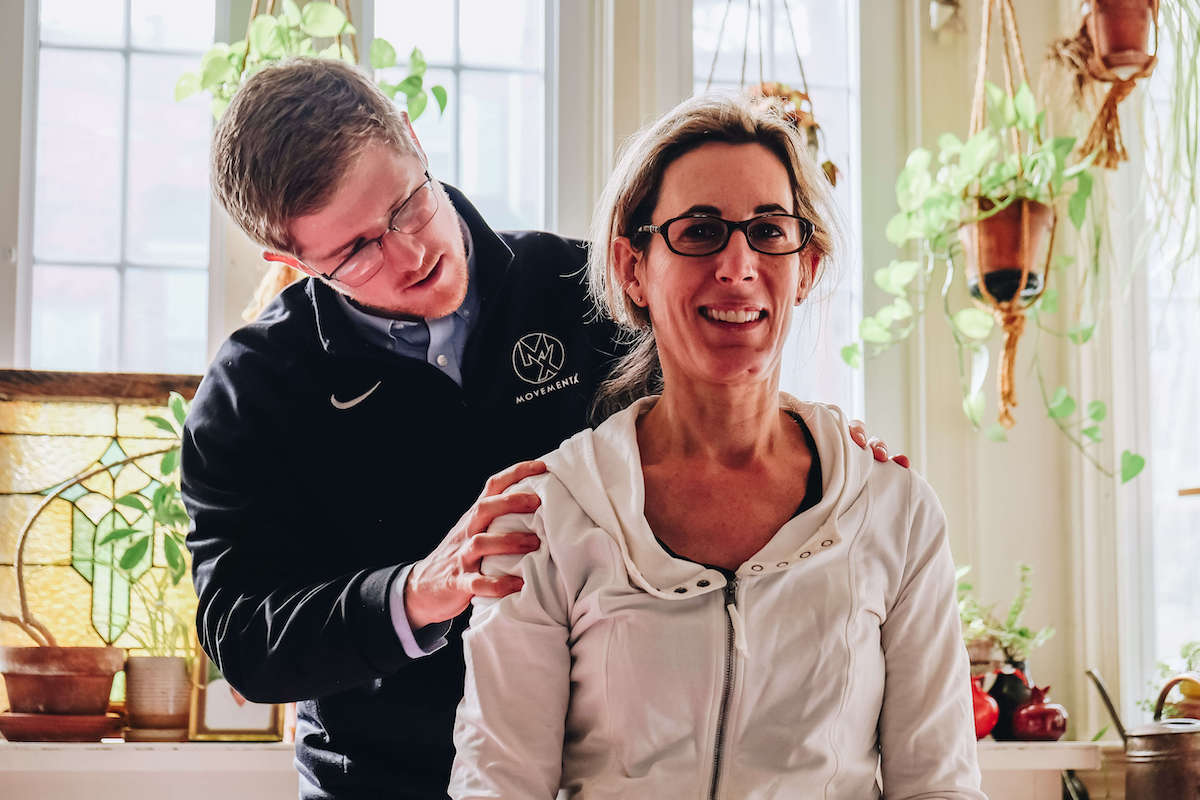 Physical therapist evaluating a woman's neck in her home in Arlington, Virginia