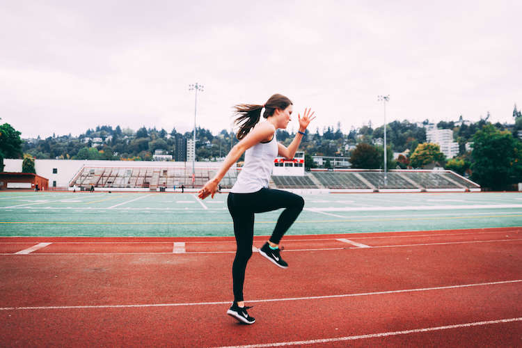 Woman with forward lean performing running drills