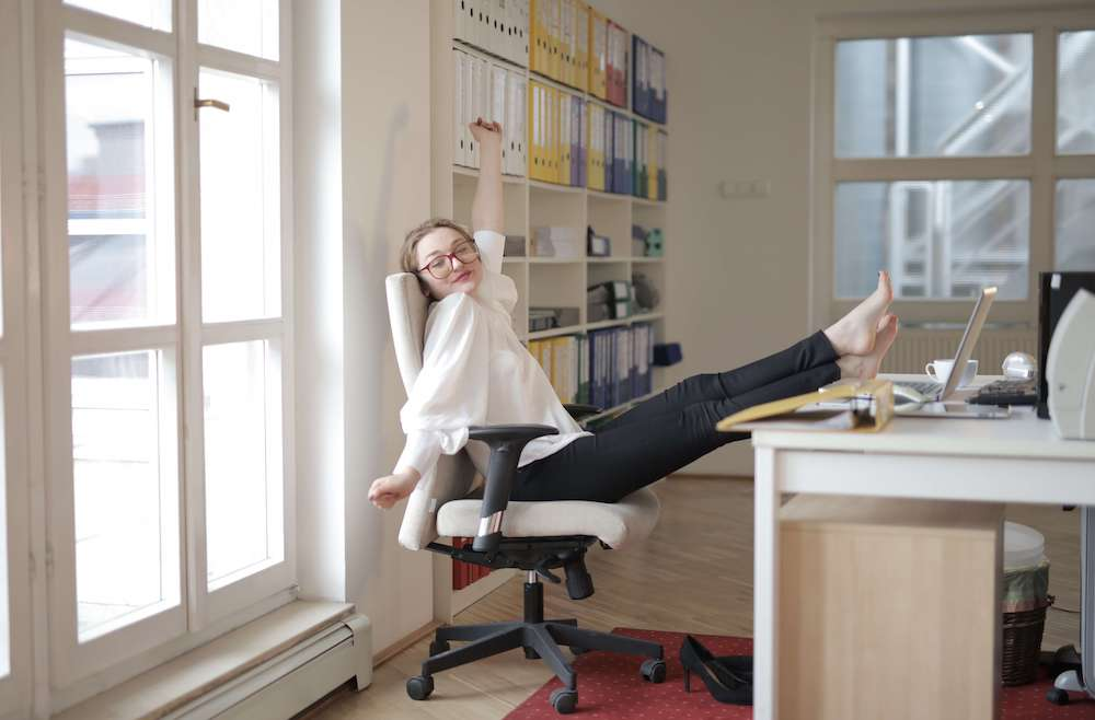 Woman moving and stretching at her desk without her shoes on
