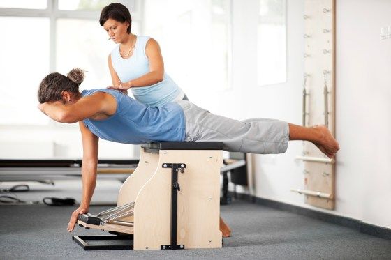Instructor helping woman with Pilates exercises on Wunda Chair.