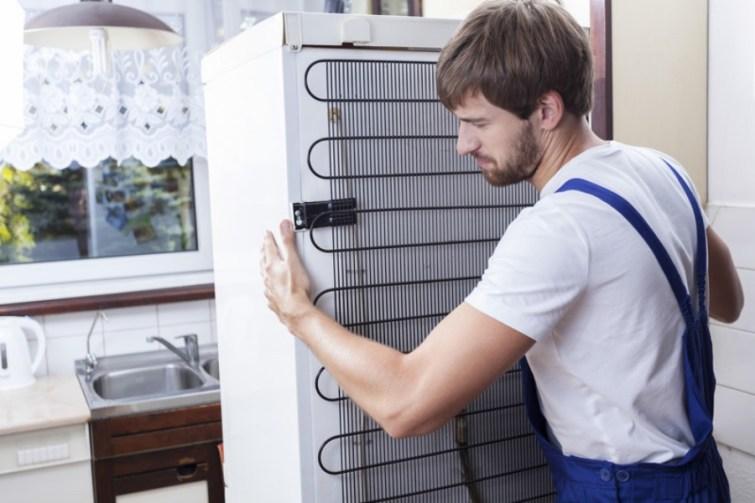 Mann transportiert Kühlschrank beim Umzug