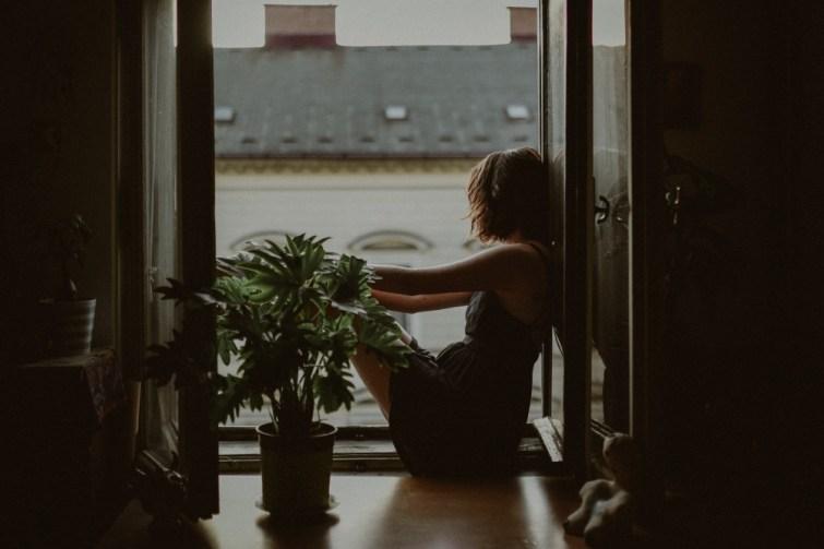 Frau mit Umzugsdepression guckt aus dem Fenster