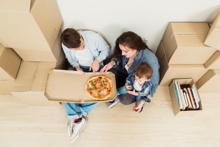 Familie isst Pizza nach dem Umzug
