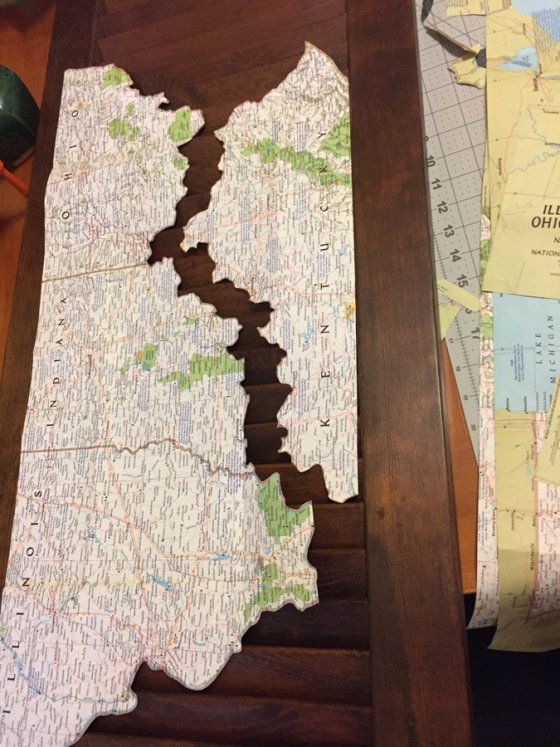 Mapping out a plan: After stain and lacquer, an old National Geographic map went under the Xacto knife.