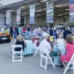 Guests on the tarmac enjoy food and drinks alongside exotic automobiles.