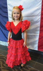 Sofia represents Spanish culture by wearing a traditional Spanish flamenco dress.