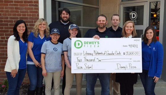 Kevin Dern, Dewey's Pizza director of community outreach, and Dewey's Clifton staff present the Literacy Network with a check from the Pizza School: Liz Priestle, Annie Schneider, Dewey's Clifton staff (in light blue and black shirts), Kevin Dern (holding check), Michelle Otten Guenther and Shannon Lienemann.