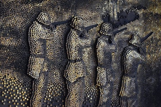 "Detail of ""Massacre"": The art installation is an interpretation of an historical photo of a Nazi firing squad engaged in a mass shooting. The mosaic was constructed using tens of thousands of bullet casings. This genocide by mass shooting, which killed approximately  2 million Jews, has been called a ""Holocaust by bullets."""