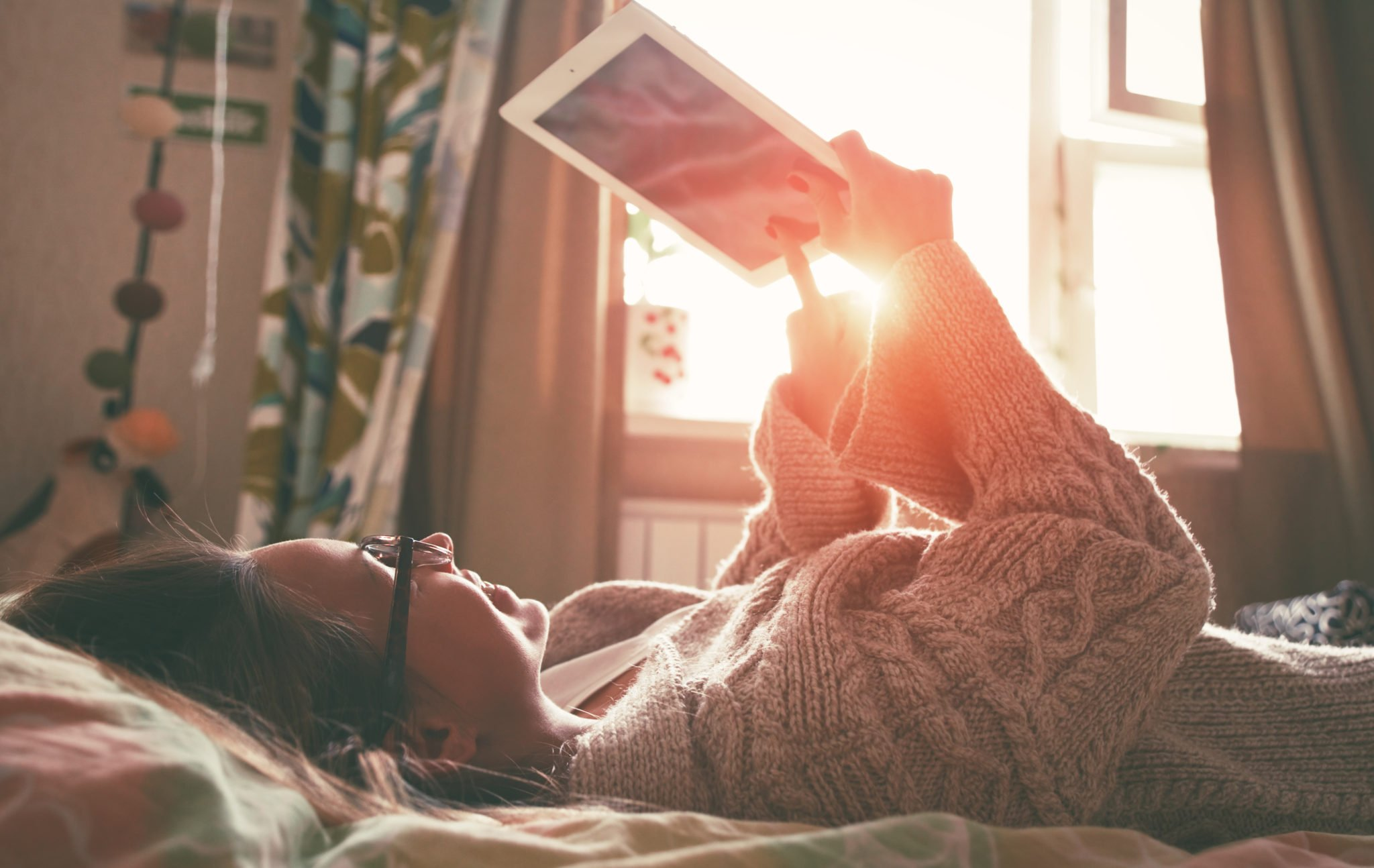 woman lying in bed with digital tablet touching with finger in morning sunlight