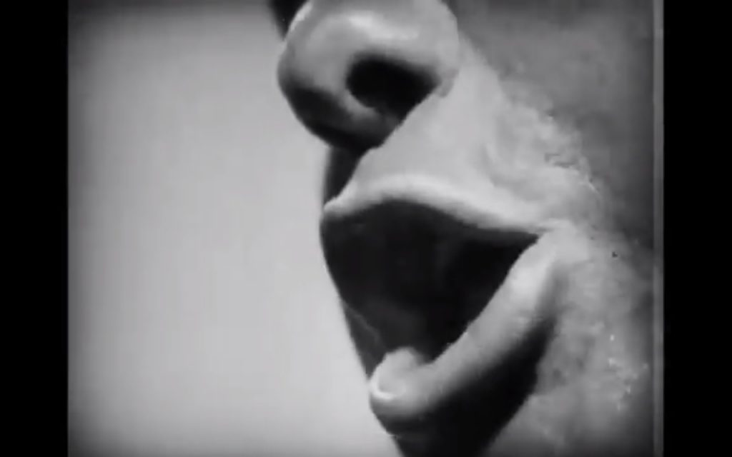 An extreme close-up of a priest's mouth dehumanizes his character.