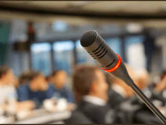 Photo of a microphone against a blurred background in a room with people