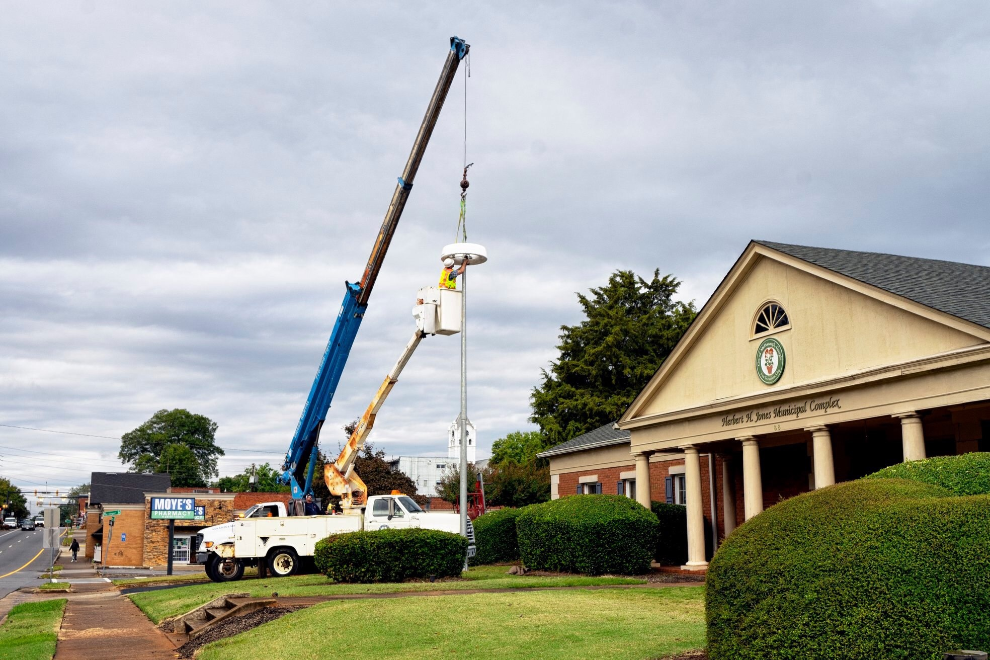 Photo of McDonough staff installing a solar-powered light outside McDonough Fire Station 51 (city photo)