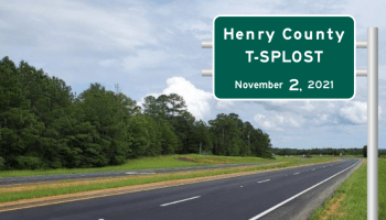 """Photo of a four-lane road in Georgia with a custom road sign overlay """"Henry County T-SPLOST November 2, 2021"""" (Georgia DOT photo / Sign Maker by Brendon Strowe)"""