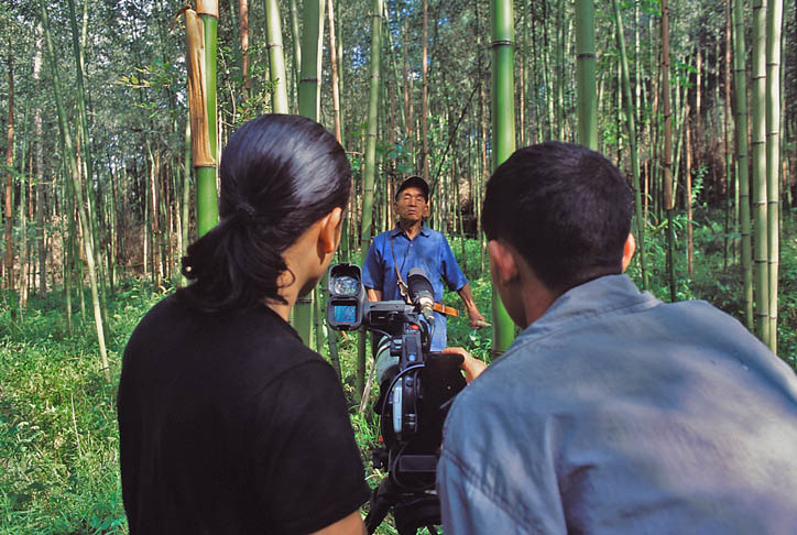 Hage Komo gets video instructions from Moji Riba, who is enlisting local young people to capture the oral histories, languages and rituals of their tribes for his project. Komo films his father gathering bamboo in a grove outside Hari Village. (Photo courtesy Rolex Awards)
