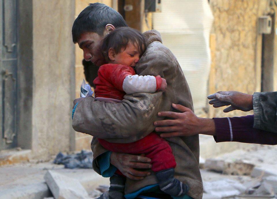 Un garçon sauve sa petite sœur des débris de leur maison en Syrie.