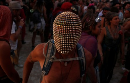 A participant wears a mask as he dances as approximately 70,000 people from all over the world gathered for the annual Burning Man arts and music festival in the Black Rock Desert of Nevada