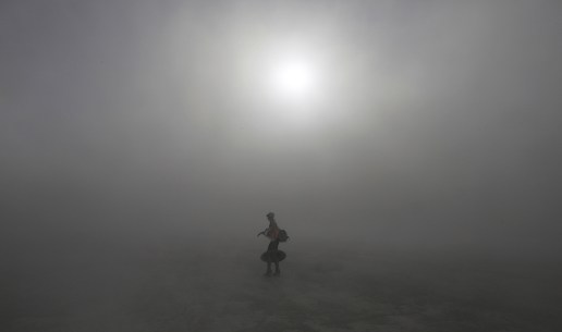Burning Man participant walks through a desert dust storm during the Burning Man arts and music festival in the Black Rock Desert of Nevada