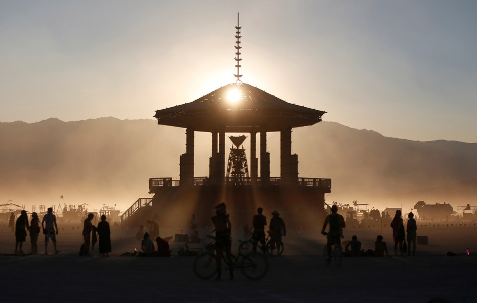 Participants watch the sun set behind the Man as approximately 70,000 people from all over the world gathered for the annual Burning Man arts and music festival in the Black Rock Desert of Nevada