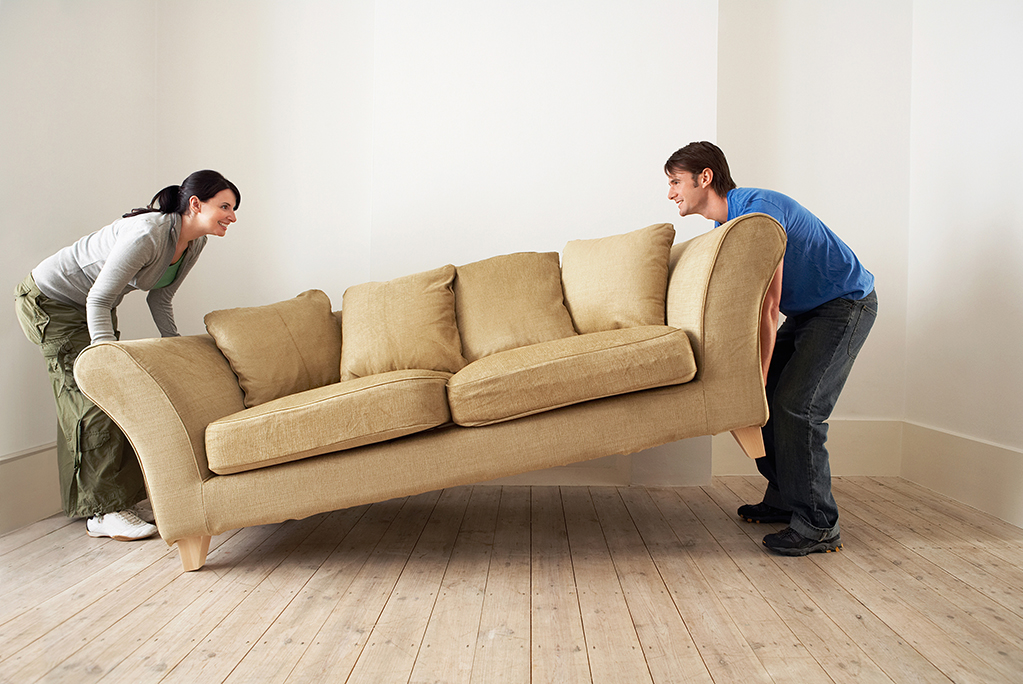 couple moving couch for donation