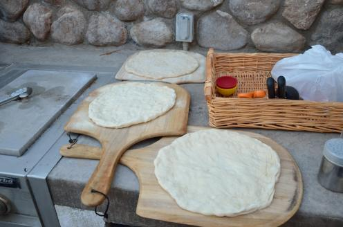 Pizza doughs laid out on pizza peels, awaiting their ingredients.