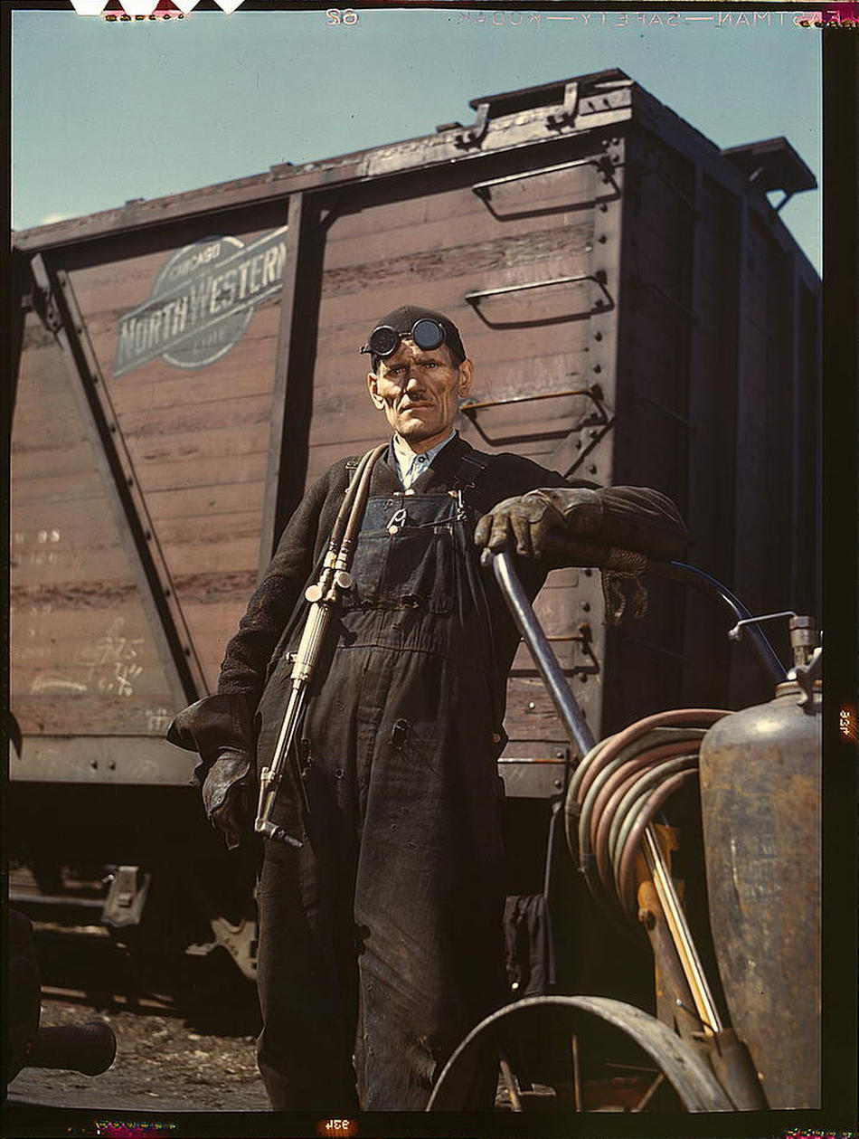 Mike Evans, a welder, at the rip tracks at Proviso yard of the Chicago and Northwest Railway Company. Chicago, Illinois, April 1943. Reproduction from color slide. Photo by Jack Delano. Prints and Photographs Division, Library of Congress.