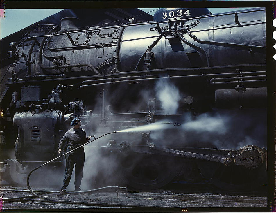 "Mrs. Viola Sievers, one of the wipers at the roundhouse giving a giant ""H"" class locomotive a bath of live steam. Clinton, Iowa, April 1943. Reproduction from color slide. Photo by Jack Delano. Prints and Photographs Division, Library of Congress"