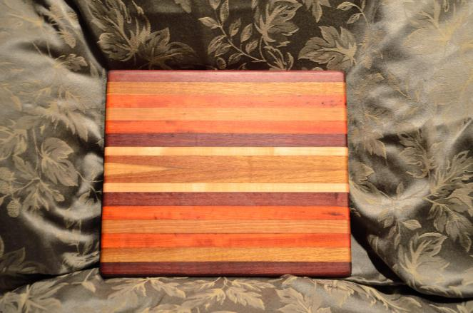 This colorful board was requested by MrsMowry. Canarywood, Hard Maple, Purpleheart and Cherry.
