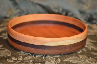 This simple bowl is made from Honey Locust (on top), Walnut and Cherry. The color variation in the Honey Locust is due to sapwood in the piece that I used ... that's a feature, not a defect!