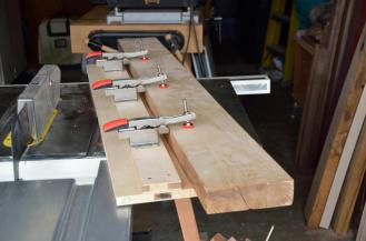 This straightening jig holds the rough-edged board as you send it through the table saw. As seen here, the left edge of the jig will slide along the table saw fence to provide a square edge as a guide ...