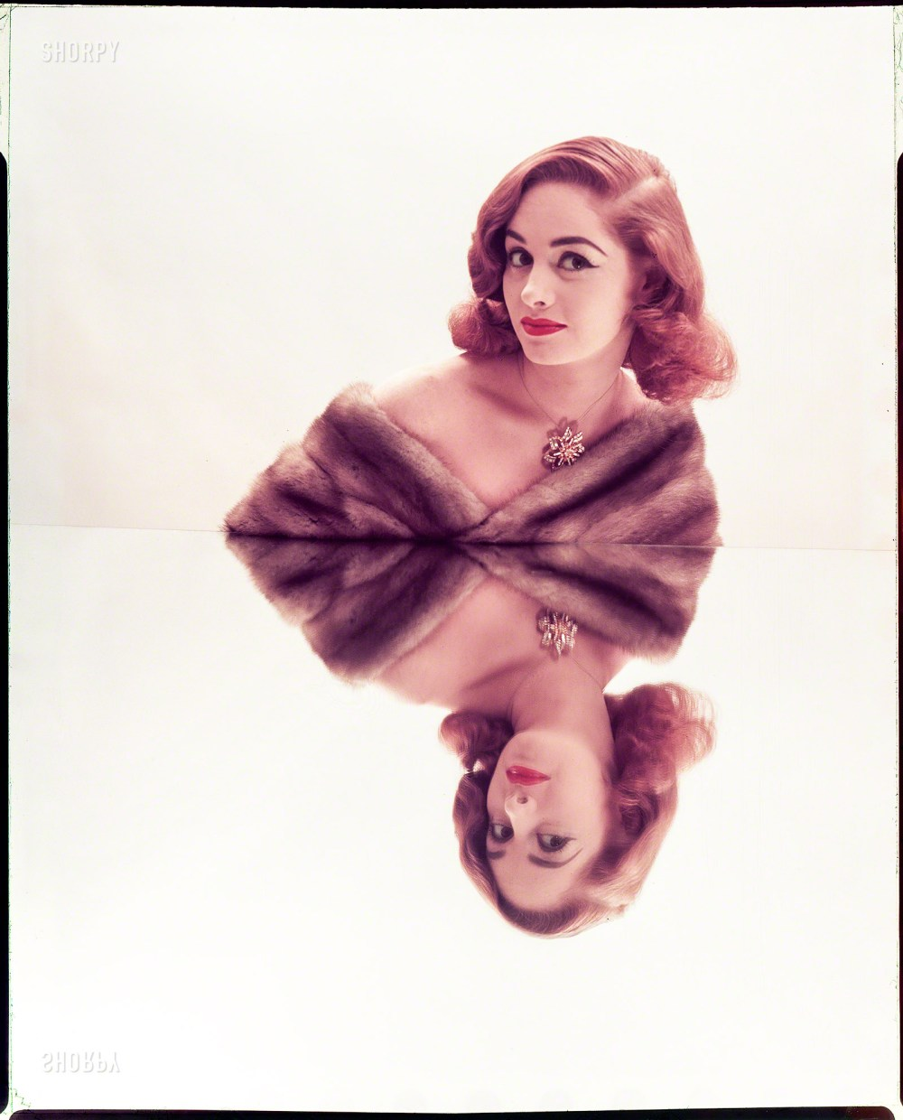 "July 1952. ""Photographs show models posed leaning shoulders against mirrors, resulting in reflected images. Includes women wearing furs and jewels; various hairstyles."" Color transparency by Louis Faurer for the Look magazine assignment ""Reflected Beauty: Hair Now Gets Double Exposure."" From Shorpy Historical Photos; see link below."